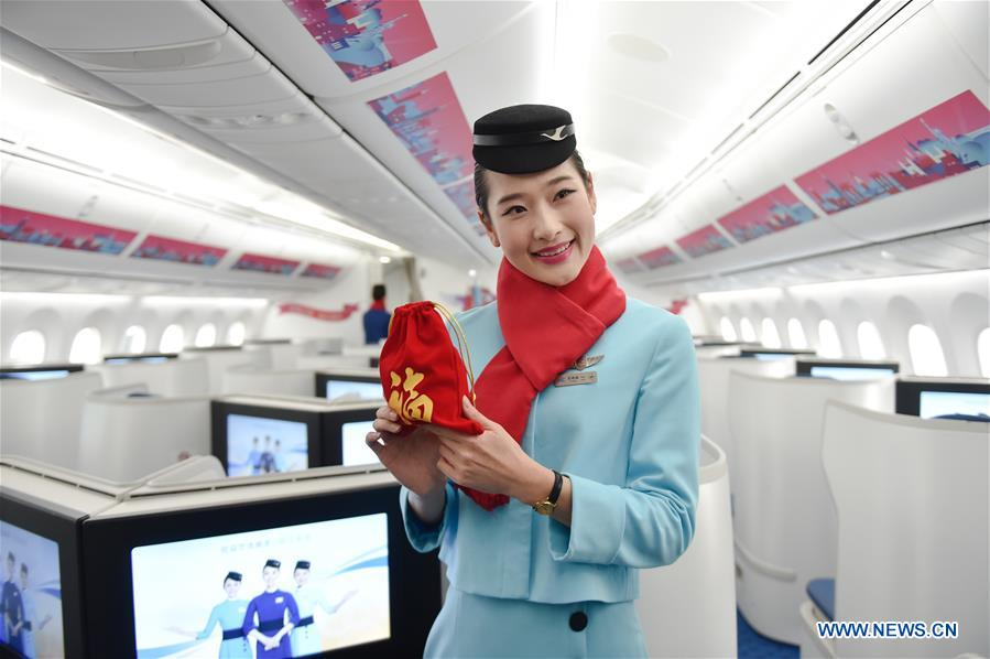 A stewardess shows a gift prepared for passengers on the flight MF849 at the Fuzhou International Airport in Fuzhou, capital of southeast China's Fujian Province, Feb. 15, 2017. MF849, the first direct flight of Xiamen Airlines from Fuzhou to New York, took off here on Wednesday.