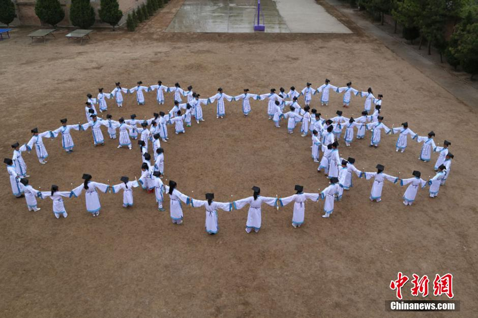 "Pupils in Hanfu practice ""Wushu calligraphy exercise"" in N China's Gansu Province"