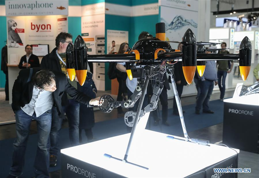 A visitor inspects a drone displayed at the ProDrone booth during the CeBIT 2017 in Hanover, Germany, on March 20, 2017. The world's leading trade fair showcasing IT and communications products and solutions CeBIT 2017 kicked off on Monday and will last until March 24. The show with the theme 'd!conomy - no limits' this year attracted around 3,000 exhibitors from 70 countries and regions and is expected to attract some 200,000 visitors. (Xinhua/Shan Yuqi)