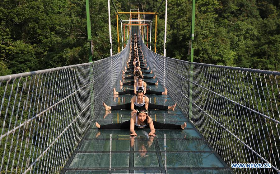 Yoga lovers practice yoga on glass bridge at Shuanglonggou forest park