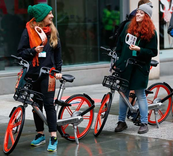 Two women ride Mobikes in Manchester in the United Kingdom. [Photo/Xinhua]