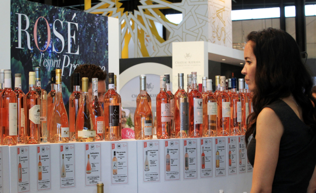 A woman looks bottles of rose wine at the international wine fair