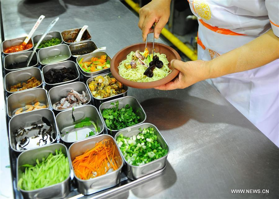 Quan Fujian prepares meals for customers at his restaurant in Yantai City, east China's Shandong Province, June 7, 2018. Fushan noodle is a traditional dish which is popular in Shandong Province. The noodle is hand pulled and cooked with various sauces and broths. The making of Fushan noodle was listed as a provincial intangible cultural heritage of Shandong in 2013. (Xinhua/Ren Pengfei)