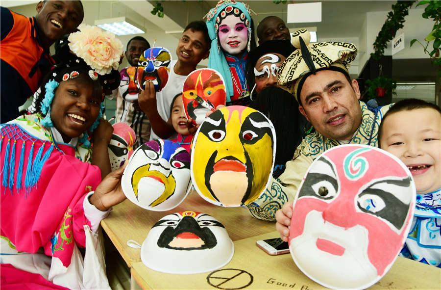 Foreign students and children show Peking Opera masks they painted in Zhenjiang city, Jiangsu Province, on July 9, 2018.  (Photo/Asianewsphoto)