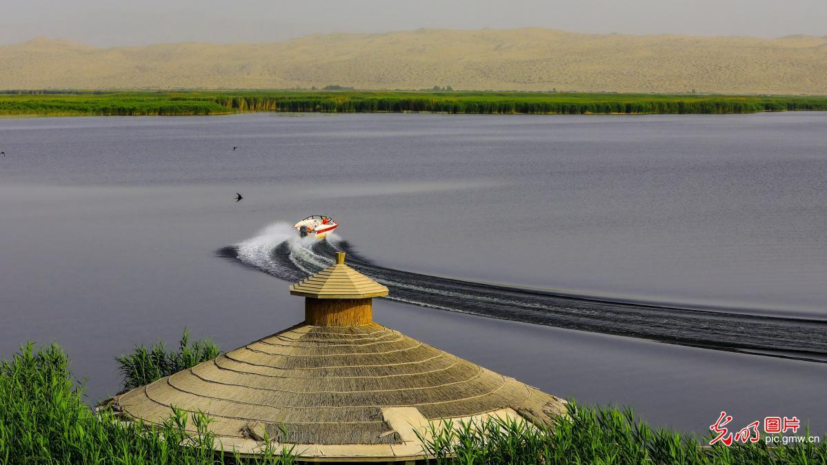 Tourists enjoy beautiful scenery of Bosten Lake, NW China's Xinjiang