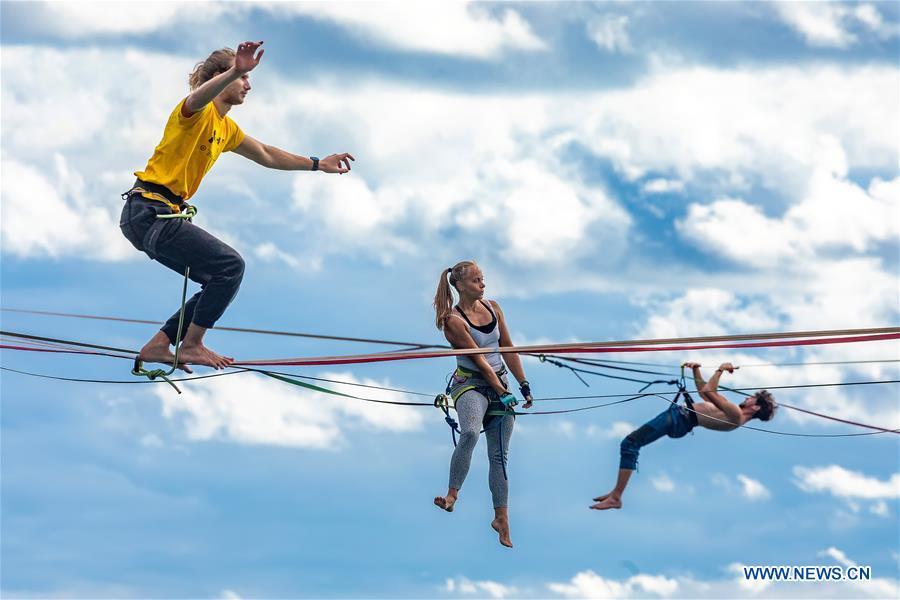 People practise rope-walking above Gortanova Bay in Pula, Croatia