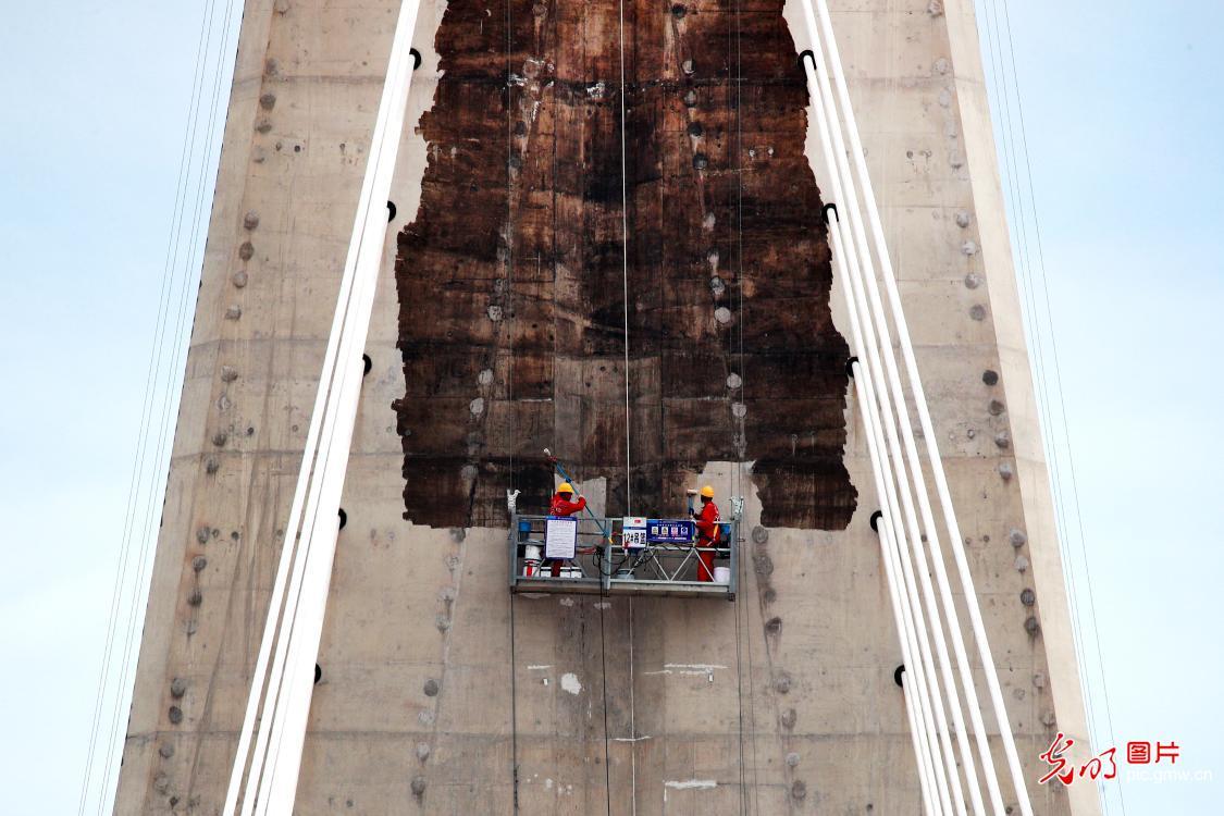 Workers coating main bridge towers of Zhoudai Bridge in E China's Zhejiang Province