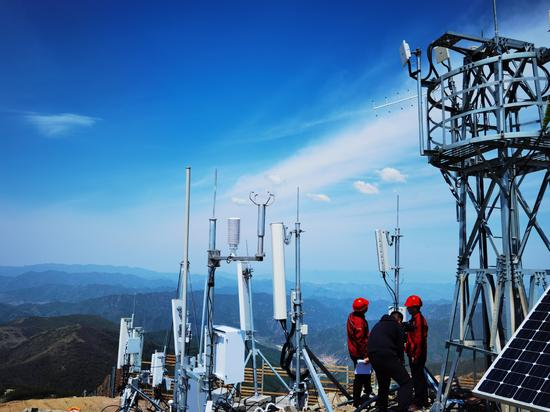 Technicians with the Beijing branch of China Tower Corp work at a 5G base station in Beijing. (Photo provided to China Daily)