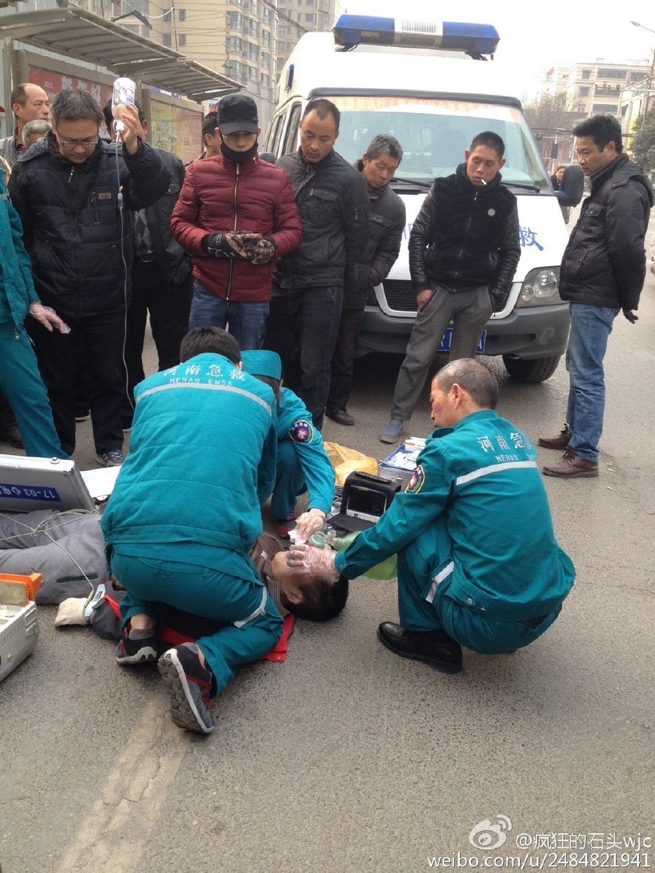 男子骑车晕倒 路人轮流举吊瓶抢救