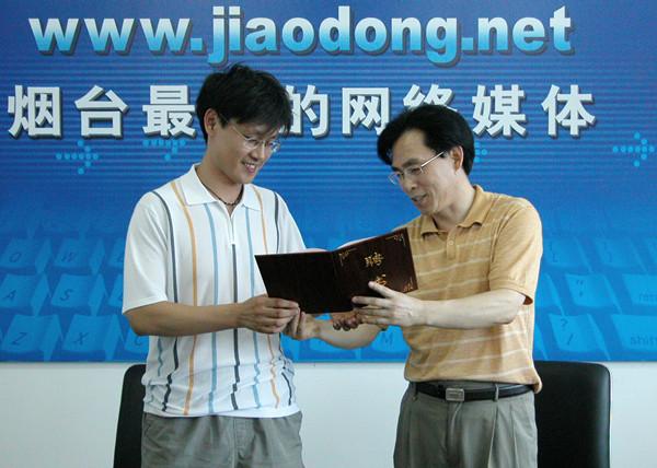 2005年7月,作者(右)给鲁东社区球迷俱乐部特邀技术顾问丁刚先生颁发聘书。