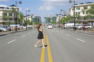 2013年7月17日,哈巴格希新村,一名女子穿过马路。