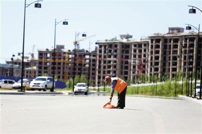 7月17日,康巴什新区,一名清洁工在清扫街道。