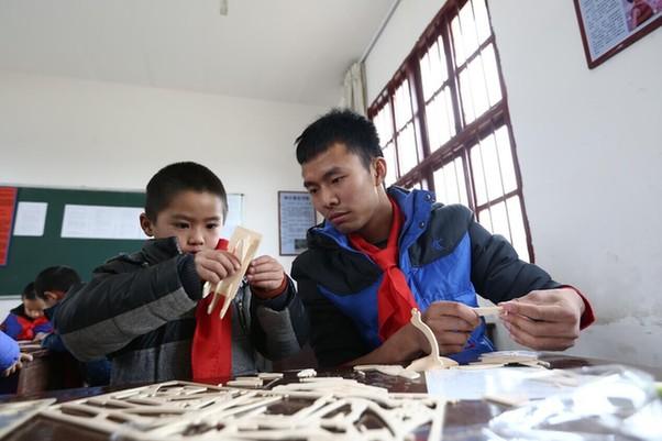 志愿者和小学生一起做手工模型