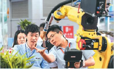 近日,在哈尔滨国际装备制造业博览会上,一家参展企业工作人员(右)在介绍机械臂。